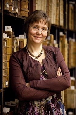 Librarian Veronique Verspeurt in front of a bookshelf with sixteenth-century books